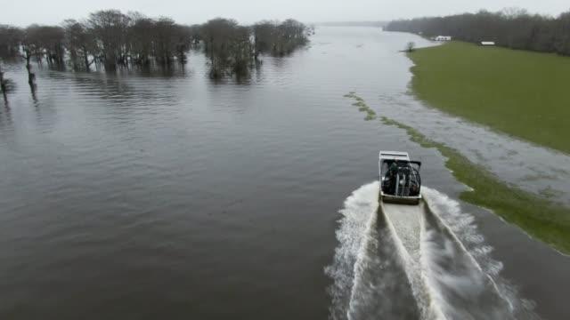 vidéos et rushes de tir de drone aérien d'un tour airboat, excès de vitesse par flottant salvinia (fern) dans le marais de bassin de rivière atchafalaya dans le sud de la louisiane sous un ciel couvert - louisiane