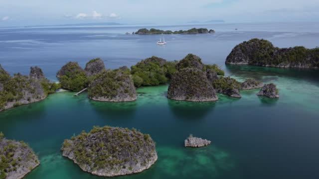 aerial drone shot of an archipelago and sailboat - indonesia islands stock videos & royalty-free footage