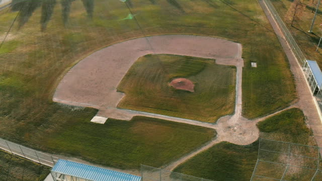 aerial drone shot of an empty baseball field/ diamond at sunset/sunrise - baseball diamond stock videos and b-roll footage