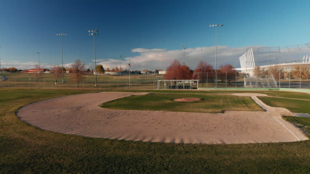 aerial drone shot of an empty baseball field/diamond and complex with salt lake city, utah mountains in the background under a blue sky at sunset/sunrise - baseball diamond stock videos and b-roll footage