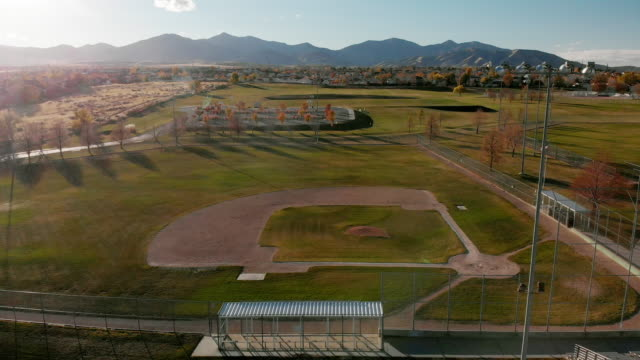aerial drone shot of an empty baseball field/diamond with salt lake city mountains in the background at sunset/sunrise - baseball diamond stock videos and b-roll footage