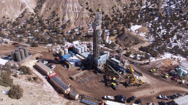 aerial drone shot of an oil and gas drilling pad site in a valley in winter on a sunny day - land stock videos & royalty-free footage