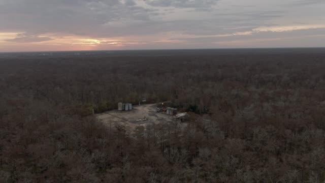 aerial drone shot of an oil & gas drilling pad in a thick forest of cypress trees in swamp wetlands in southern louisiana at sunrise under an overcast sky - overcast stock videos & royalty-free footage