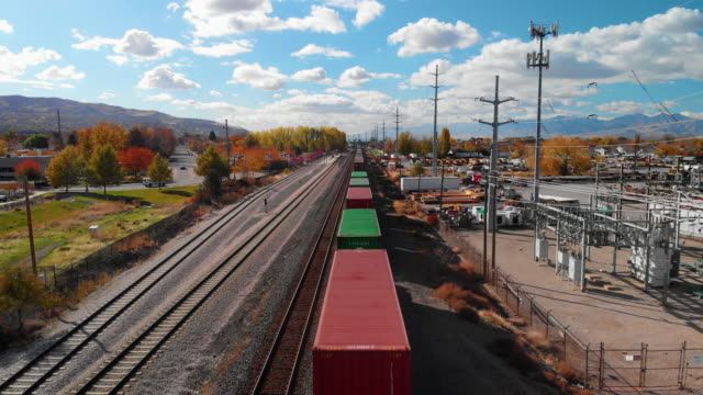 aerial drone shot of an oncoming train beside a road and a power station in salt lake city under a clouded but sunny sky - railway track stock videos & royalty-free footage
