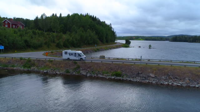 aerial: drone shot of camper van on bridge against sky - asunden, sweden - lago video stock e b–roll