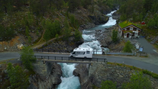 vidéos et rushes de aerial: drone shot of camper van on bridge over flowing river in forest - oppland, sweden - transport