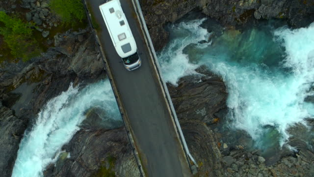 aerial: drone shot of camper van on bridge over flowing river - oppland, sweden - camper van stock videos & royalty-free footage