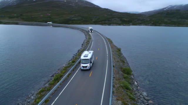 aerial: drone shot of camper vans moving on highway road amidst lake - breiddalsvatnet, norway - camper van stock videos & royalty-free footage