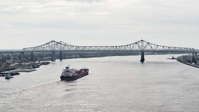 aerial drone shot of cargo river/steamboat sailing along the mississippi river toward the crescent city connection bridge next to downtown new orleans on an overcast day - river mississippi stock videos & royalty-free footage