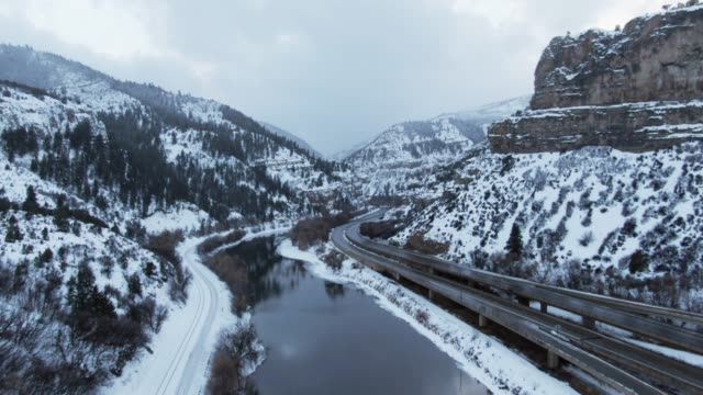 aerial drone shot of cars and vehicles driving on interstate 70 in the rocky mountains of colorado next to the colorado river on a snowy, overcast winter day - colorado stock videos & royalty-free footage