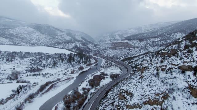 stockvideo's en b-roll-footage met luchtfoto drone schot van auto's en voertuigen die rijden op 70 tusen staten in de rocky mountains van colorado naast de colorado rivier op een besneeuwde, bewolking winterdag - interstate snelweg amerika