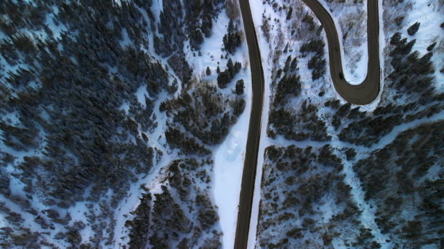 aerial drone shot of cars driving along a curvy, snowy red mountain pass (road: million dollar highway) in the san juan mountains (rocky mountain range) outside of ouray, colorado in winter surrounded by a forest of trees - winding road stock videos & royalty-free footage