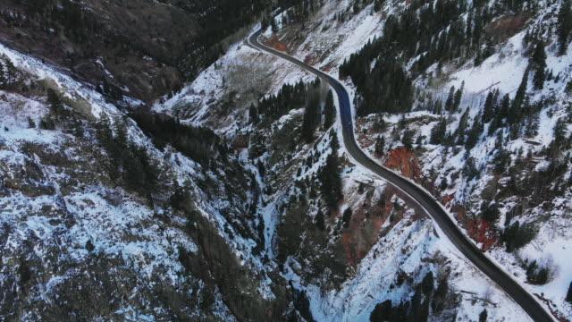 赤山雪道を走る車の空中ドローン ショット (道路: 百万ドル高速道路) サンファン山脈 (ロッキー山脈) の森の木々 に囲まれた冬のユーレイ、コロラド州の外で - ユアレイ市点の映像素材/bロール