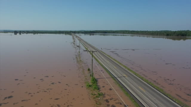 stockvideo's en b-roll-footage met aerial drone shot of cars driving down a roadway surrounded by flood water in dardanelle arkansas - environment or natural disaster or climate change or earthquake or hurricane or extreme weather or oil spill or volcano or tornado or flooding