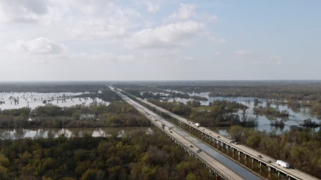 aerial drone shot of flying around breaux bridge (interstate 10) and the atchafalaya river basin swamp surrounded by cypress tree forests in southern louisiana under a sunny but partly cloudy sky - bog stock videos & royalty-free footage