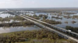 Aerial Drone Shot of Flying around Breaux Bridge (Interstate 10) and the Atchafalaya River Basin Swamp Surrounded by Cypress Tree Forests in Southern Louisiana Under a Sunny but Partly Cloudy Sky