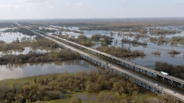 colpo di drone aereo che vola intorno al ponte breaux (interstate 10) e alla palude del bacino del fiume atchafalaya circondata da foreste di cipressi nel sud della louisiana sotto un cielo soleggiato ma parzialmente nuvoloso - louisiana video stock e b–roll