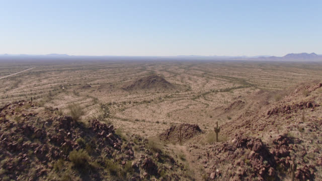 aerial drone shot of flying over a mountain peak to reveal the valley below in the sonoran desert national monument in arizona on a clear, sunny day - general view stock videos & royalty-free footage