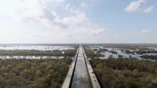 vídeos de stock, filmes e b-roll de drone aerial shot de sobrevoar breaux bridge (interestadual 10) e o pântano de bacia do rio atchafalaya rodeado por florestas de ciprestes no sul da louisiana sob um céu ensolarado, mas nublado - perspectiva espacial