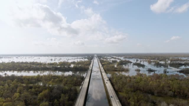 aerial drone shot of flying over breaux bridge (interstate 10) and the atchafalaya river basin swamp surrounded by cypress tree forests in southern louisiana under a sunny but partly cloudy sky - louisiana stock videos & royalty-free footage