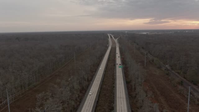 aerial drone shot of highway 90 running through a thick forest of cypress trees in swamp wetlands in southern louisiana near new orleans at sunrise under an overcast sky - overcast stock videos & royalty-free footage