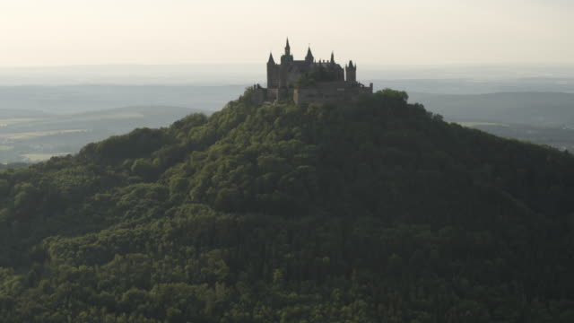 vídeos y material grabado en eventos de stock de aerial drone shot of hohenzollern castle and surrounding forest at sunset - castillo estructura de edificio