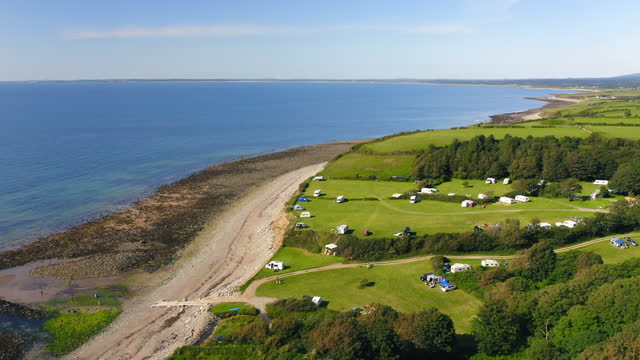 aerial drone shot of idyllic green farmland and fields on coast of wales on sunny summer day with low tide ocean and beach - camping stock videos & royalty-free footage
