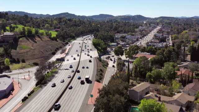 aerial: drone shot of land vehicles on roads in city during summer - woodland hills, california - urban road stock videos & royalty-free footage