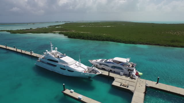 vidéos et rushes de aerial drone shot of luxury super yachts in the bay / provodenciales, turks and caicos islands - bahamas
