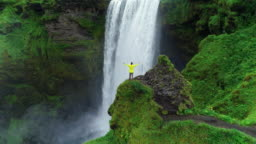 Aerial drone shot of man with arms raised on top of cliff standing in front of waterfall celebrating