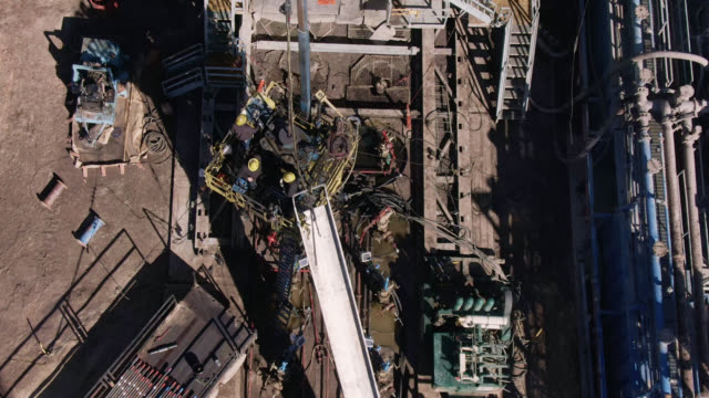 aerial drone shot of oilfield workers servicing a well at an oil and gas drilling pad site on a sunny day - drill stock videos & royalty-free footage