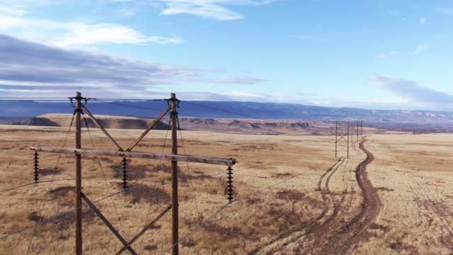 aerial drone shot of power lines above a dirt road and a field of brown grass with the colorado national monument in the background in western colorado under a partly cloudy sky - power line stock videos & royalty-free footage