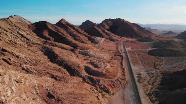 aerial drone shot of red desert mountains next to lake mead road (road leading into and out of las vegas, nevada) - autostrada interstatale americana video stock e b–roll