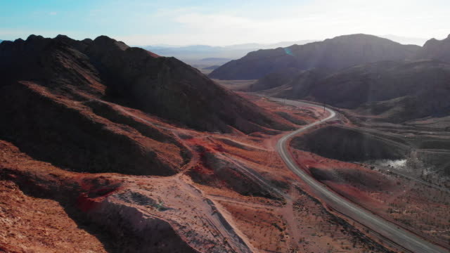 vídeos de stock e filmes b-roll de aerial drone shot of red desert mountains next to lake mead road (road leading into and out of las vegas, nevada) - estrada de ferro