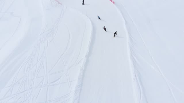 aerial drone shot of snowboarders going down the slope la plagne ski resort, tarentaise, savoy, french alps, france, europe - deep snow stock videos & royalty-free footage