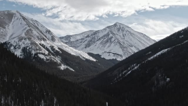 aerial drone shot of snowcapped mountains of the rocky mountains in colorado under a partially cloudy but sunny winter sky - montagne rocciose video stock e b–roll