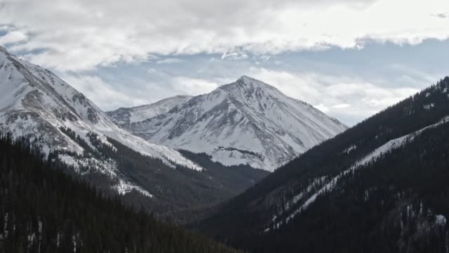 aerial drone shot of snowcapped mountains of the rocky mountains in colorado under a partially cloudy but sunny winter sky - mountain range stock videos & royalty-free footage