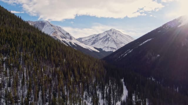 aerial drone shot of snowcapped mountains of the rocky mountains in colorado under a partially cloudy but sunny winter sky - snowcapped mountain stock videos & royalty-free footage