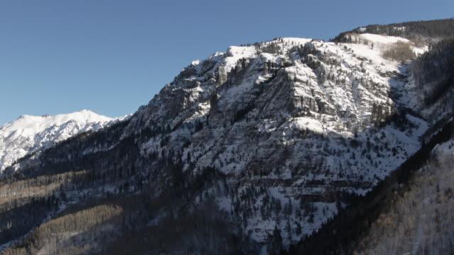 サンファン山脈 (ロッキー山脈) 青空の下でユーレイ、コロラド州の外の雪を頂いた山の空中ドローン ショット - ユアレイ市点の映像素材/bロール