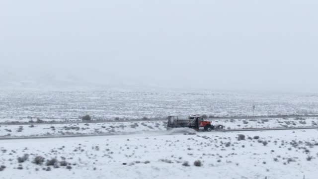 aerial drone shot of snowplow driving along a highway through a snowy, rocky desert landscape in winter under an overcast sky - snowplough stock videos & royalty-free footage