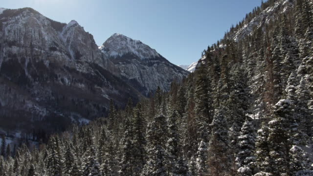 aerial drone shot of snowy forests of trees and snowcapped peaks of the san juan mountains (rocky mountains) outside of ouray, colorado under a clear sky - snowcapped mountain stock videos & royalty-free footage