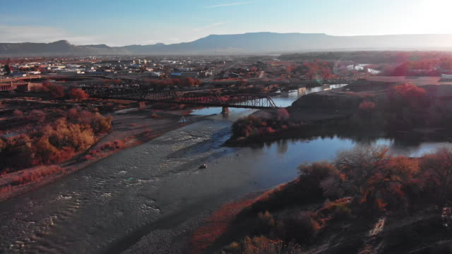 aerial drone shot of the confluence (meeting) of the colorado and gunnison rivers in the middle of the town of grand junction, colorado in autumn with mt. garfield and the grand mesa in the background - rail transportation stock videos & royalty-free footage