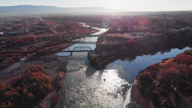 vídeos de stock e filmes b-roll de aerial drone shot of the confluence (meeting) of the colorado and gunnison rivers in the middle of the town of grand junction, colorado in autumn with mt. garfield and the grand mesa in the background - rio colorado