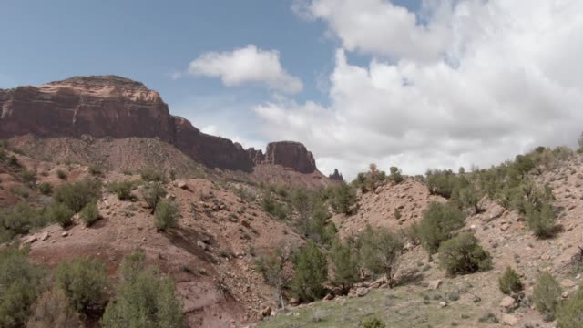 aerial drone shot of the high desert cliffs and valley outside gateway in western colorado under a partly cloudy sky - colorado stock videos and b-roll footage