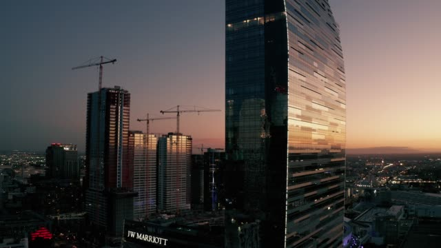 vídeos de stock, filmes e b-roll de aerial drone shot of the ritz carlton skyscraper in downtown los angeles with the setting sun on the horizon in the background and the urban sprawl... - ritz carlton hotel
