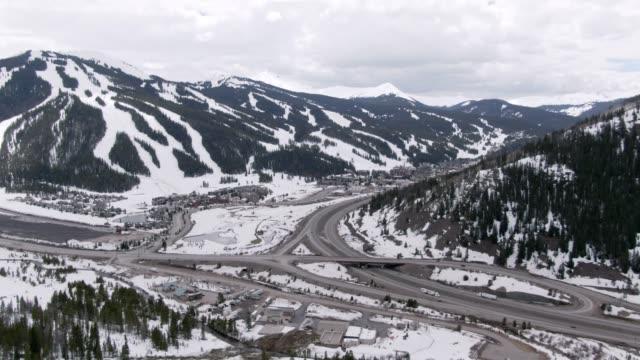 vidéos et rushes de drone aérien tiré des pentes de ski de copper mountain, colorado en hiver sous un ciel partiellement nuageux avec interstate 70 en cours d'exécution à travers elle - neige fraîche