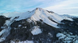 Aerial Drone Shot of the Snowy Peaks of the San Juan Mountains (Rocky Mountain Range) Outside of Ouray, Colorado in Winter Surrounded by a Forest of Trees on a Winter Morning