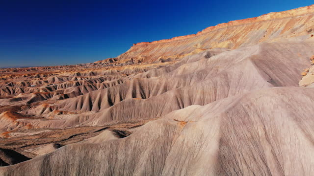 aerial drone shot of the striped, eroded sandstone cliffs of the bookcliffs (geological formation) and mt. garfield in the high desert of grand junction and palisade, colorado against a vibrant blue sky - geology stock videos & royalty-free footage