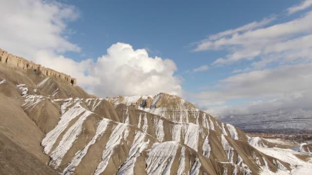 vídeos y material grabado en eventos de stock de toma aérea drone de los acantilados de piedra arenisca erosionadas, rayas de la mt. garfield en el desierto alto de grand junction y palisade, colorado en un día nevado, parcialmente nublado - grand junction