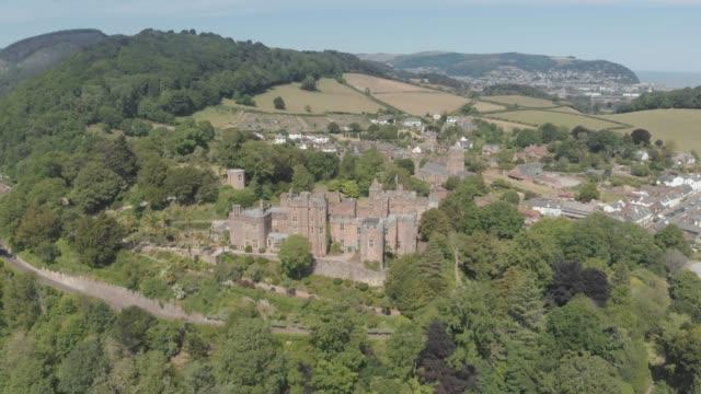 aerial drone shot of the village of dunster near minehead, england, united kingdom. - etwa 11. jahrhundert stock-videos und b-roll-filmmaterial